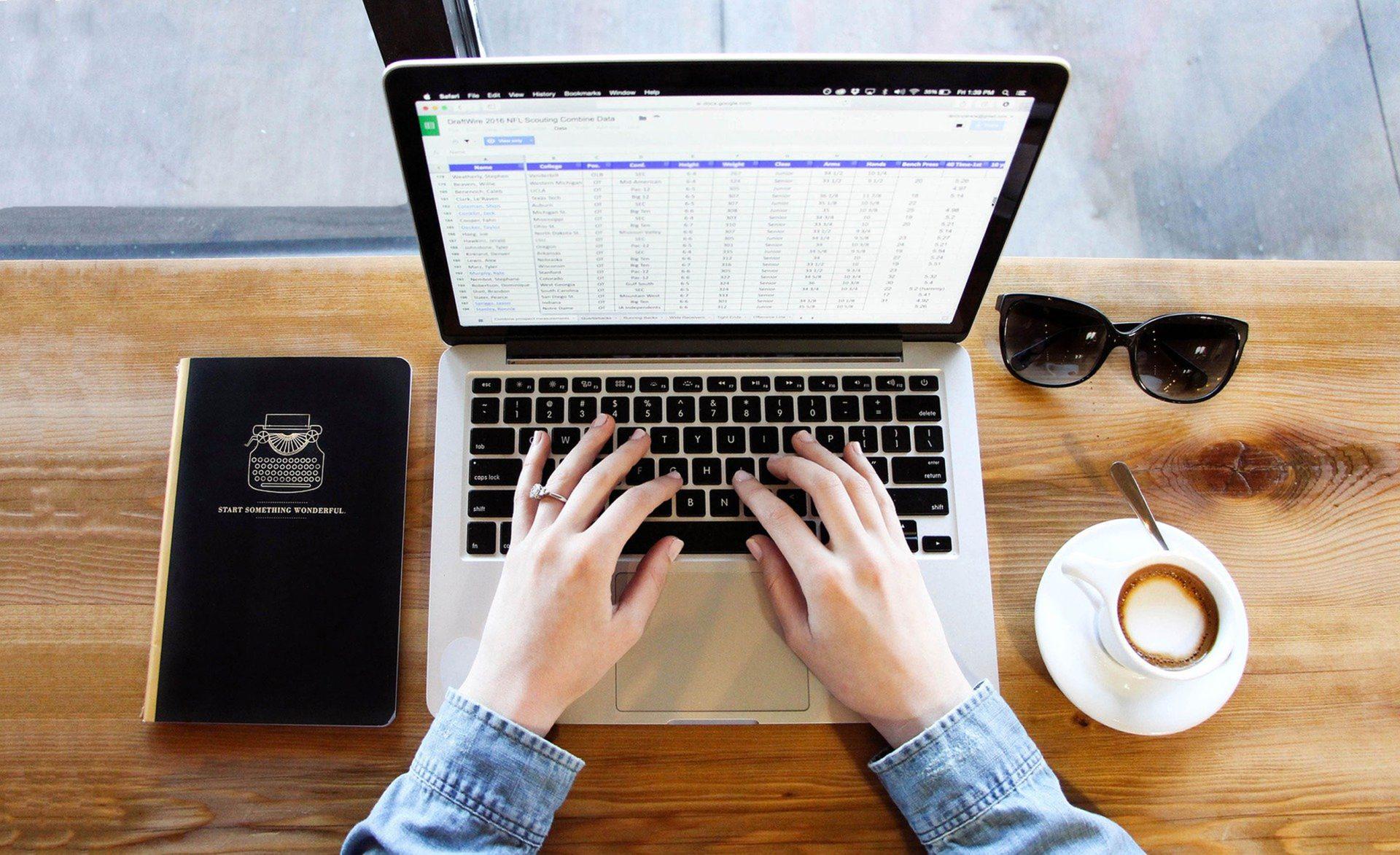 persoon achter notebook voor online training met kop koffie